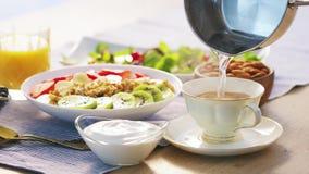 Café turco vazando água quente café da manhã saudável do muesli granola fruta fresca kiwi morango yougurt e suco video estoque