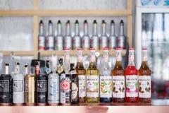 Café und Stange mit selektivem Fokus auf der Reihe von Sirupflaschen Monin lizenzfreie stockbilder