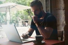 Café urbain travaillant concentré d'ordinateur portable de Wearing Black Tshirt de jeune homme d'affaires barbu Café en bois se r image libre de droits