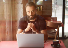 Café urbain travaillant d'ordinateur portable de Wearing Black Tshirt de jeune homme d'affaires barbu Écoute en bois se reposante photographie stock libre de droits