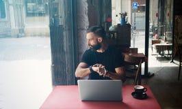 Café urbano de trabajo del ordenador portátil de Wearing Black Tshirt del hombre de negocios barbudo joven Mirada de madera del c Fotos de archivo libres de regalías
