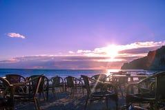 Café vacío en la puesta del sol por el mar Foto de archivo