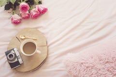 Café, vieil appareil-photo de vintage dans le lit sur les feuilles roses Roses et carnets autour Espace de travail indépendant de Photo libre de droits