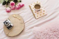 Café, vieil appareil-photo de vintage dans le lit sur les feuilles roses Roses et carnets autour Espace de travail indépendant de Photo stock