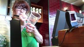 Café y barista de compra del cliente que anotan nombre en la taza almacen de metraje de vídeo