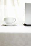 Café y computadora portátil en el mantel blanco Fotografía de archivo libre de regalías