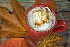 Café y crema azotada en la hoja del otoño Fotos de archivo