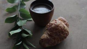 Café y cruasán del capuchino en fondo de madera en la tabla Desayuno perfecto por la mañana Estilo rústico almacen de metraje de vídeo