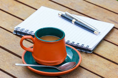 Café y cuaderno y plumas calientes Fotografía de archivo libre de regalías