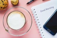 Café y cuaderno y un teléfono en una tabla rosada Imagen de archivo