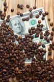 Café y dinero en una tabla de madera Ganancias en el café Imagen de archivo libre de regalías