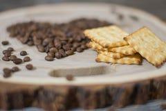 Café y galletas del grano en un corte de madera Imagen de archivo libre de regalías
