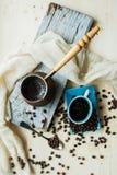 Café y granos de cobre del cezve en un fondo de acero imagen de archivo