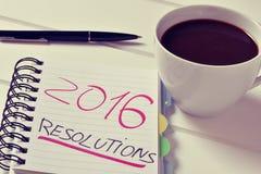 Café y libreta con las resoluciones del texto 2016 Foto de archivo