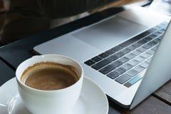 Café y ordenador portátil de la falta de definición en el fondo de madera de la tabla en café Fotos de archivo libres de regalías
