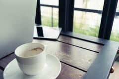 Café y ordenador portátil de la falta de definición en la tabla en estilo retro Fotos de archivo