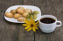 Café y placa con la hornada, en una tabla de madera Fotografía de archivo