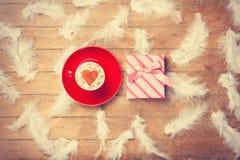 Café y plumas con el regalo en fondo de madera Imágenes de archivo libres de regalías