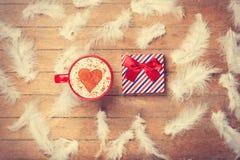 Café y plumas con el regalo en fondo de madera Fotos de archivo libres de regalías