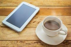 Café y tableta calientes en la tabla de madera Foto de archivo libre de regalías