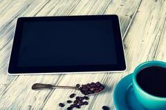 Café y tableta en la tabla foto de archivo