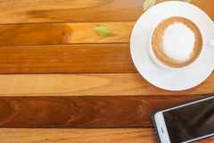 Café y teléfono móvil en una tabla de madera Fotos de archivo