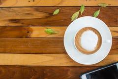 Café y teléfono móvil en una tabla de madera Imágenes de archivo libres de regalías
