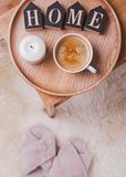 Café y vela en la bandeja de madera que se coloca en el nigthstand y los deslizadores rosados en el piso foto de archivo