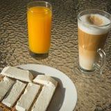 Café, zumo de naranja y biscote curruscante con queso blanco suave Imagen de archivo