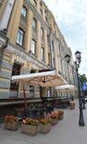 Cafés al aire libre acogedores cerca del edificio viejo hermoso Fotos de archivo libres de regalías