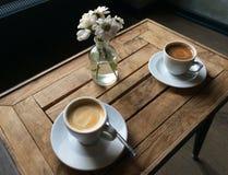 Cafés en la tabla con las flores foto de archivo