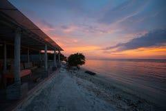 Cafés et plage sur le rivage de la mer au coucher du soleil Photos libres de droits