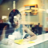 Caféstadt-Lebensstilfrau auf trinkendem Kaffee des Telefons Lizenzfreie Stockfotografie