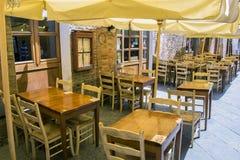 Cafétabellen und -stühle außerhalb eines wunderlichen Backsteinbaus in Toskana, Italien Stockbild