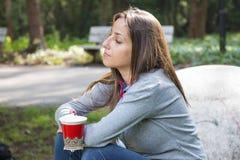Café bebendo da jovem mulher bonita em um parque da manhã Imagem de Stock