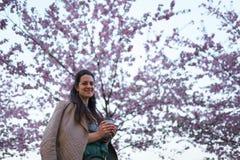 Caf? bebendo da jovem mulher de um copo de papel que veste a saia esmeralda da cor - flor de cerejeira colorida de sakura em um p foto de stock royalty free