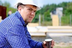 Café bebendo do trabalhador em seu capacete de segurança Fotografia de Stock Royalty Free