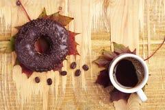 Café, buñuelo y hojas de otoño Imagen de archivo