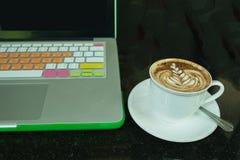 Café caliente en la taza y platillo y cuaderno blancos Foto de archivo