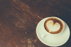 Café com teste padrão do coração em um copo branco no fundo de madeira Foto de Stock Royalty Free
