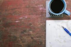 Café con el cuaderno de notas manchado y pluma con el espacio de la copia Imágenes de archivo libres de regalías