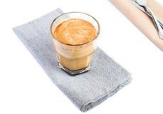 Café con leche en una taza de cristal en el mantel de lino aislado encendido Fotos de archivo