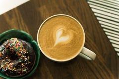 Caf? con leche y un bu?uelo imagenes de archivo