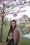 Caf? de consumici?n de la mujer joven de una taza de papel que lleva la falda esmeralda del color - flor de cerezo colorida de Sa foto de archivo