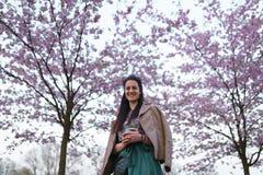 Caf? de consumici?n de la mujer joven de una taza de papel que lleva la falda esmeralda del color - flor de cerezo colorida de Sa fotos de archivo