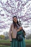 Caf? de consumici?n de la mujer joven de una taza de papel que lleva la falda esmeralda del color - flor de cerezo colorida de Sa fotografía de archivo libre de regalías