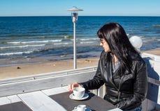 Caf? de consumici?n de la mujer morena joven en un caf? al aire libre cerca del mar imagenes de archivo