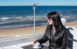 Caf? de consumici?n de la mujer morena joven en un caf? al aire libre cerca del mar imagen de archivo libre de regalías