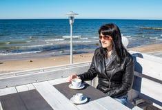 Caf? de consumici?n de la mujer morena joven en un caf? al aire libre cerca del mar fotos de archivo libres de regalías