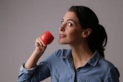 Café de consumición de la mujer de la pequeña taza roja Fotografía de archivo